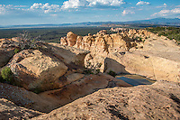 El Malpais National Monument - SandStone Bluffs<br /> Sandstone Bluffs overlook an ancient lava flow at El Malpais National Monument near Grant New Mexico. The area has had volcanic activity dating from 115,000 years ago to as recent as 3000 years ago. Puebloan Indians have lived in the area for 10,000 years and continue their ancestral uses, including gathering herbs and medicines and other ceremonial activities.<br /> <br /> El Malpais National Monument is new to the National Park System, having been established in 1987, it contains 114,277 acres. El Malpais translates to &quot;the badlands&quot; in Spanish and is pronounced Mal-(rhymes with wall)-pie-ees.<br /> <br /> After rainfalls, the potholes, or tinajas, fill with water and create temporary miniature ecosystems. Fairy shrimp, tadpole shrimp, spadefoot toad tadpoles and water insects find homes in these tiny oases. The tinajas atop of the bluffs undoubtedly supplied people with water as well.