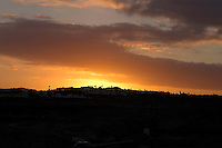 Pink and gold clouds against background of properties on Golf del Sur. Tenerife, Canary Islands.