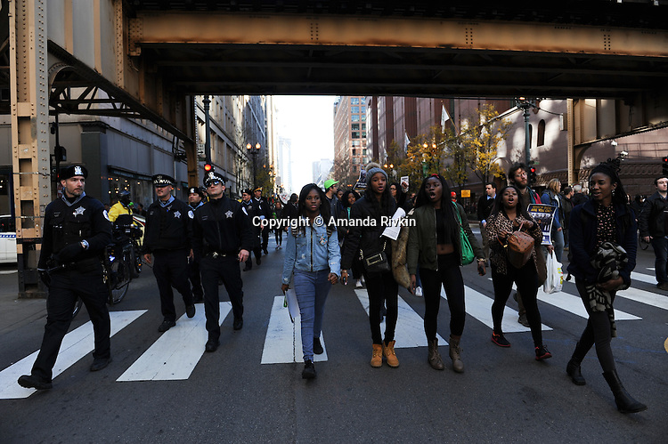 Police and protesters calling on Chicago Mayor Rahm Emanuel to resign march up State Street in the Loop in Chicago, Illinois on December 9, 2015.  Emanuel offered a historic apology for the police killing of Laquan McDonald and police brutality and racial profiling generally -- without using those words -- in front of the City Council in the morning.