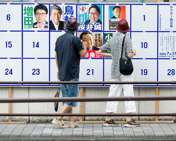 A couple is studying election candidates' posters