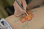 Brooklyn, New York, USA. 10th August 2013. Volunteer artist Laura Yorburg uses colorful makeup to paint flowers on a young woman's leg during the 3rd Annual Coney Island History Day celebration.