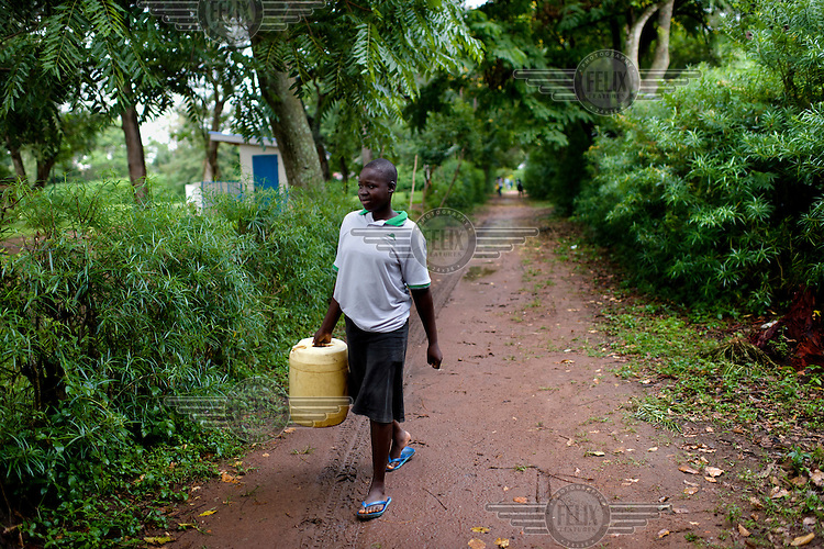 Margaret Kigeni (14), on her way to fetch water from a borehole, a student at Achilet Primary School.