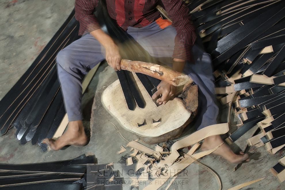 A worker cuts up leather belts in a small factory in Kanpur.