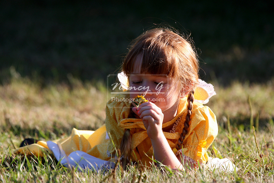 A young girl looking at a flower