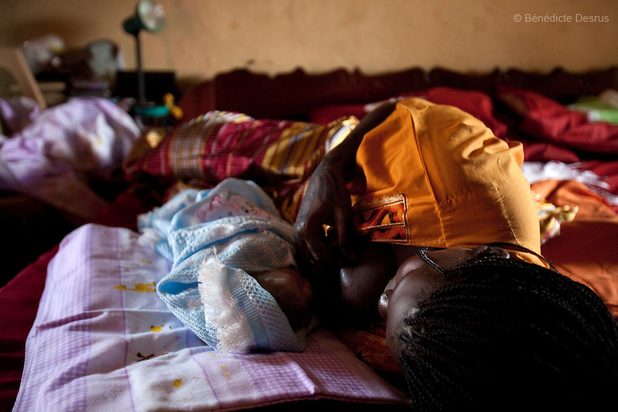 July 18, 2011 - Juba, Republic of South Sudan - Lushi Rashid, a 29 year old muslim South Sudanese woman, breast feeds her new born baby boy at her family home with the help of Regabia Ahmad, a qualified birth attendant, in Juba, the capital city of South Sudan. Regabia has been delivering babies in South Sudan for over twenty years. she was trained by the health ministry and works at a local primary health clinic. With fewer than 100 trained midwives for a population of over eight million, South Sudan has the highest maternal mortality rate in the world.  One in seven South Sudanese women is likely to die because of complications from delivery. Just 10 per cent of South Sudanese women have access to medical professionals during childbirth. Photo credit: Benedicte Desrus