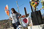 Miho Suzuki, 43, whose daughter Kana was swept away with 73 fellow elementary school students and teachers during the March 11 tsunami, visits an ad hoc  shrine outside her daughter's school in Ishinomaki, Miyagi Prefecture, Japan on 07 Sept. 2011. Photograph: Robert Gilhooly
