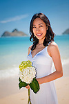 Asian bride poses with bouquet of flowers during honeymoon on Lanikai Beach, Kailua, Hawaii