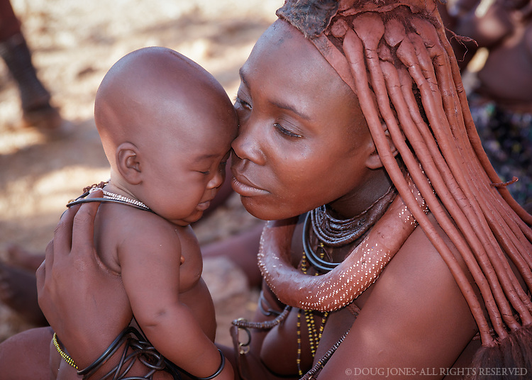 This Himba mother and her baby live in a village in Kaokoland, near Epupa Falls on the Angola border in northern Namibia.  She coats her skin and the skin of her baby with a mixture of butterfat and ochre, producing a satin reddish sheen.  The region is one of the wildest and least populated areas of the country. Approximately 5,000 Himba inhabit the region.