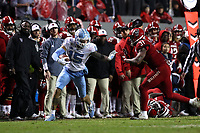 RALEIGH, NC - NOVEMBER 30: Beau Corrales #15 of the University of North Carolina fights off an attempted tackle by Jarius Morehead #31 of North Carolina State University during a game between North Carolina and North Carolina State at Carter-Finley Stadium on November 30, 2019 in Raleigh, North Carolina.