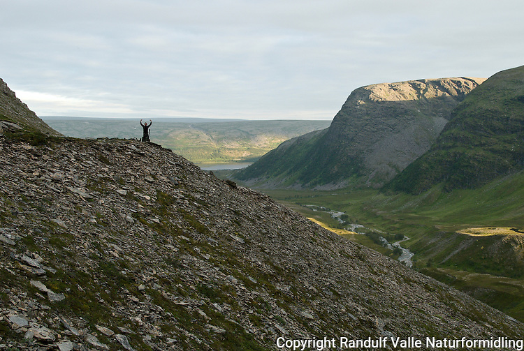 Mann går til fots i fjellandskap. ---- Man hiking in mountain landscape.