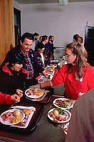 Teen serving couple Christmas dinner in church soup kitchen.  Minneapolis Minnesota USA