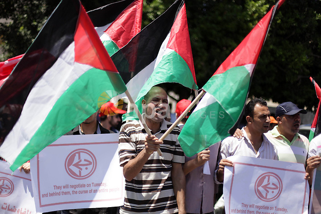 Supporters of the Popular Front for the Liberation of Palestine chant slogans during a protest against resuming peace talks with Israel in Gaza City, Sunday, July 28, 2013. The rally was held against U.S. Secretary of State John Kerry's attempt to restart Israeli-Palestinian talks after five years of diplomatic paralysis. Photo by Ashraf Amra