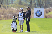 Shane Lowry (IRL) and caddy Dermot Byrne prepare to play his 2nd shot on the 9th hole during Sunday's Final Round of the 2014 BMW Masters held at Lake Malaren, Shanghai, China. 2nd November 2014.<br /> Picture: Eoin Clarke www.golffile.ie