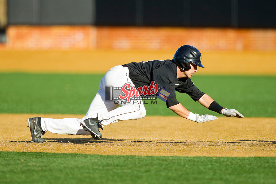 Pat Blair (11) of the Wake Forest Demon Deacons dives back to first base during the game against the West Virginia Mountaineers at Wake Forest Baseball Park on February 24, 2013 in Winston-Salem, North Carolina.  The Demon Deacons defeated the Mountaineers 11-3.  (Brian Westerholt/Sports On Film)