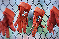 Under Armour batting gloves hang on the fence in the Frederick Keys dugout prior to the game against the Winston-Salem Dash at BB&T Ballpark on July 26, 2018 in Winston-Salem, North Carolina. The Keys defeated the Dash 6-1. (Brian Westerholt/Four Seam Images)