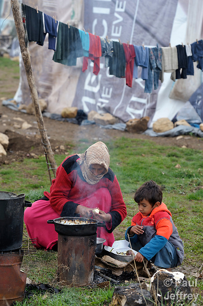 "A woman refugee from Syria prepares food for her family as her son helps her with the stove. They live in a rented ""tent""--made from a billboard canvas of a dollar bill--in the village of Jeb Jennine, in Lebanon's Bekaa Valley. They and other refugee families in the area are being assisted by International Orthodox Christian Charities and other members of the ACT Alliance.."