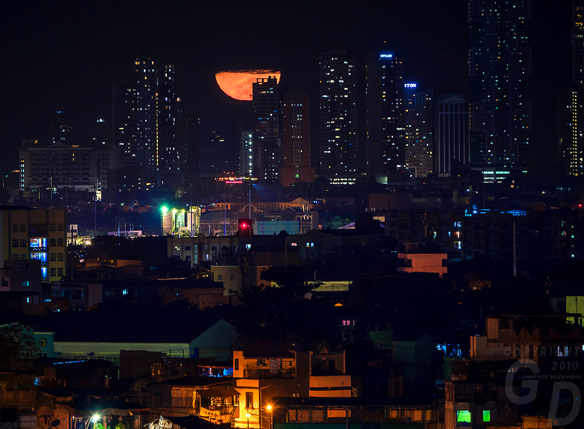 Large half moon setting over buildings in Manila, Philippines