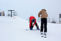 A skier and snowboarder get ready to go down the mountain at the top of the Payload triple chair at Showdown Ski Area on King's Hill in the Little Belt Mountains near Neihart, Montana, USA.