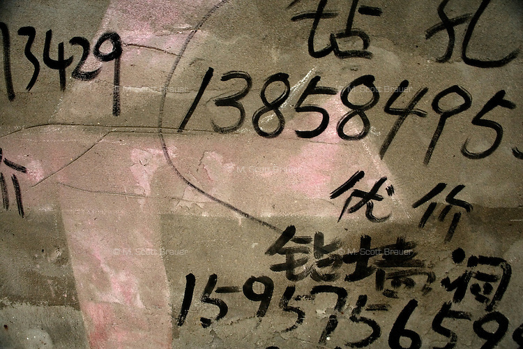 Day laborers cell phone numbers are painted on a wall in Anchang, Shaoxing County, Zhejiang Province, China.