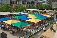 Colorful umbrellas shade diners at Mellennium Park which hosts a eatery on the edge of the park, Chigao, Illinois