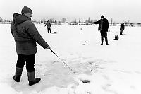 Ukraine. Province of Kiev. Slavutich. Fishermen on the frozen Dniep river. None of the men control the radioactivity level of  fishes. Radiations pass through the food chain into the human body and cause health problems. The town of Slavutich was created after the catastrophe which took place on april 1986 at 1.23 am with the explosion of reactor No 4 at Chernobyl atomic power station. Slavutich is distant 60 km from the power station and was newly built after the evacuation of the inhabitants from both towns of Pripyat and Chernobyl.  © 2006 Didier Ruef