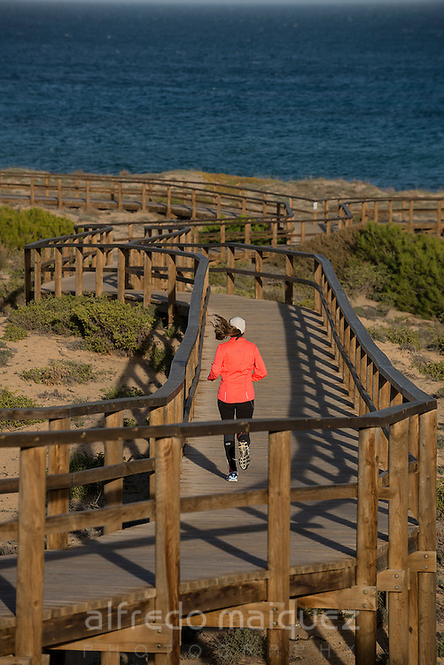 Female running along a path over the Mediterranean sea.