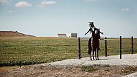 A steel silhouette cut-out of a North American Indian riding a horse placed in front of a field of genetically modified corn. This land, in south west Kansas, was once occupied by Cheyenne Indians.