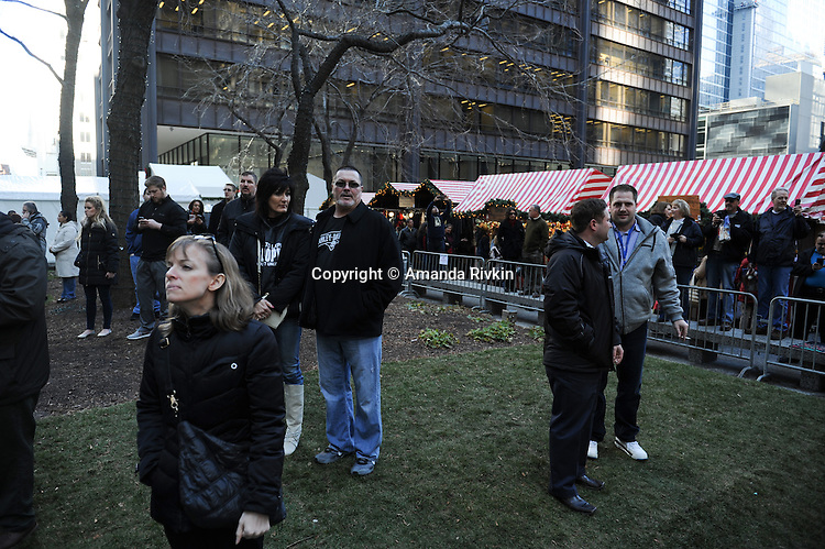 Bystanders near the Christmaskindlmarkt watch as protesters calling on Chicago Mayor Rahm Emanuel to resign stage a sit in in front of City Hall at the intersection of Washington and Clark Street in the Loop in Chicago, Illinois on December 9, 2015.  Emanuel offered a historic apology for the police killing of Laquan McDonald and police brutality and racial profiling generally -- without using those words -- in front of the City Council in the morning.