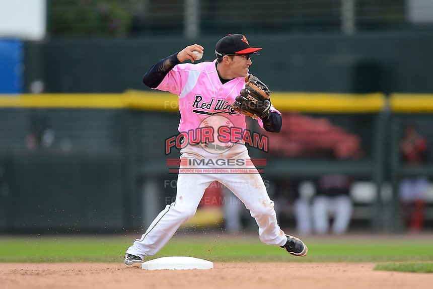 Rochester Red Wings shortstop Doug Bernier #7 attempts to turn a double play during a game against the Columbus Clippers on May 12, 2013 at Frontier Field in Rochester, New York.  Rochester defeated Columbus 5-4 wearing special pink jerseys for Mother's Day.  (Mike Janes/Four Seam Images)