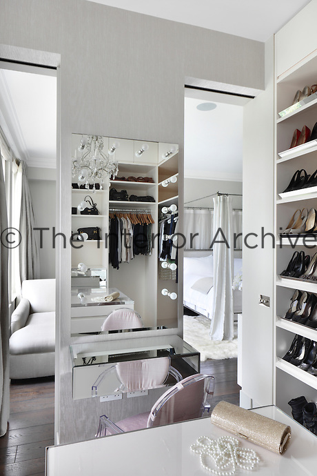 A dressing room with a stylish dressing table and mirror with integrated light bulbs