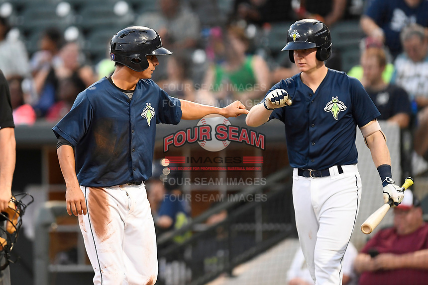 Shortstop Andres Gimenez (13) of the Columbia Fireflies, left, is congratulated by Dan Rizzie after scoring a run in a game against the Charleston RiverDogs on Monday, August 7, 2017, at Spirit Communications Park in Columbia, South Carolina. Columbia won, 6-4. (Tom Priddy/Four Seam Images)
