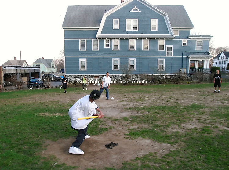 WATERBURY, CT 4/22/07- 042207BZ04- Angel Narvaez, 16, pitches to Devon Williams, 14, as T.J. Piland, 17, Brandon Hofler, 14, and Anthony Colon, 15, watch the action during a game of Wiffle Ball in a lot on the corner of Cooke Street and Pine Street in Waterbury Sunday afternoon. <br /> Jamison C. Bazinet Republican-American