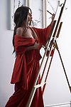 Artistic sensual portrait of a beautiful asian woman in red kimono, Japanese sumi-e artist with an easel, painting in her studio