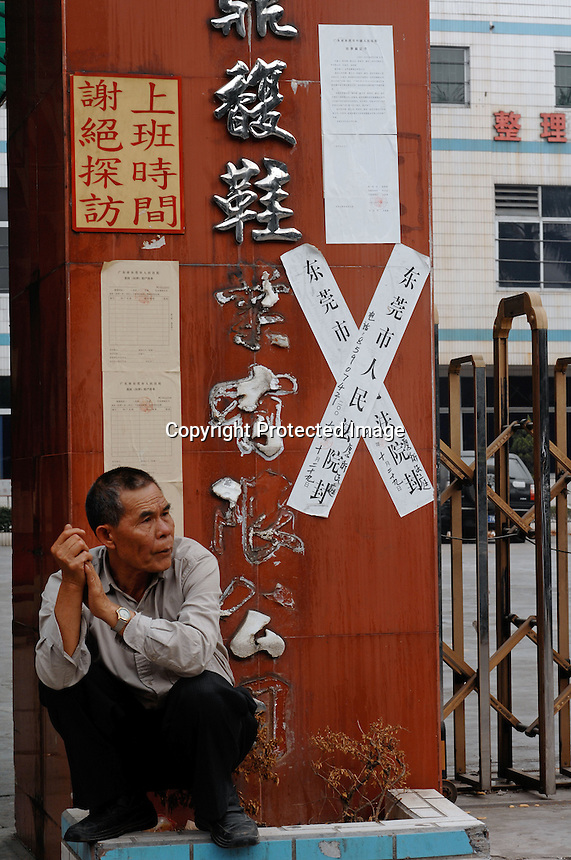 Cai Don Yi, 66, Dingfu Factory in Houjie Town, Donguan, China.  The sign outside the factory that made shoes for Zara and Nine West amongst others, reads that the &quot;Donguan People's Court have closed the factory&quot; .  As the economy changes and Chinese labour gets more expensive, factories are cosing leaving ghost towns behind them.<br /> <br /> MUST CREDIT PHOTO BY RICHARD JONES/SINOPIX