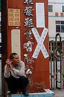 "Cai Don Yi, 66, Dingfu Factory in Houjie Town, Donguan, China.  The sign outside the factory that made shoes for Zara and Nine West amongst others, reads that the ""Donguan People's Court have closed the factory"" .  As the economy changes and Chinese labour gets more expensive, factories are cosing leaving ghost towns behind them.<br /> <br /> MUST CREDIT PHOTO BY RICHARD JONES/SINOPIX"