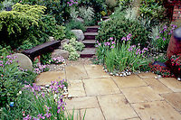 Stone patio, rustic wood bench, steps, irises. Design: Geoffrey Whiten. spring garden landscaping, shrubs, flowers, perennials