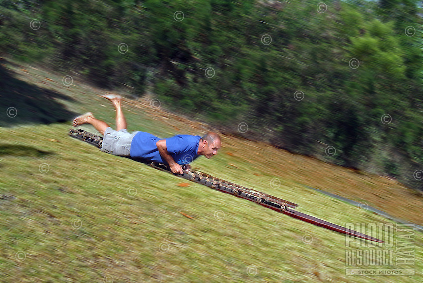 Instructor Tom Pohaku Stone demonstrates the reclining position on a holua sled. Holua was a dangerous sport practiced by ancient Hawaiians in honor of the volcano goddess, Madame Pele.