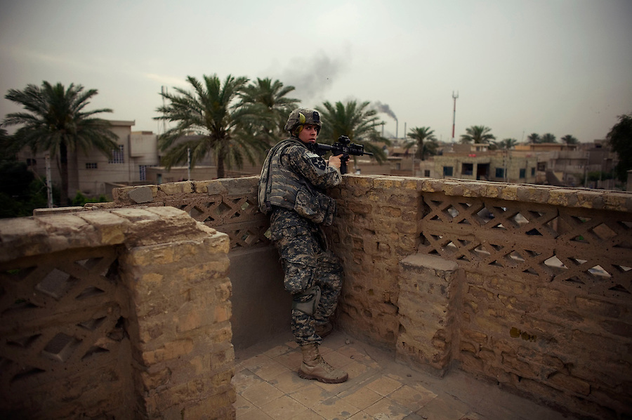 From an elevated position, a soldier with Alpha Co. 2-12 Infantry 2nd Infantry Division scans the rooftops after his platoon took sniper fire in the Dora section of south-central Bagdhad on Thursday May 10, 2007.
