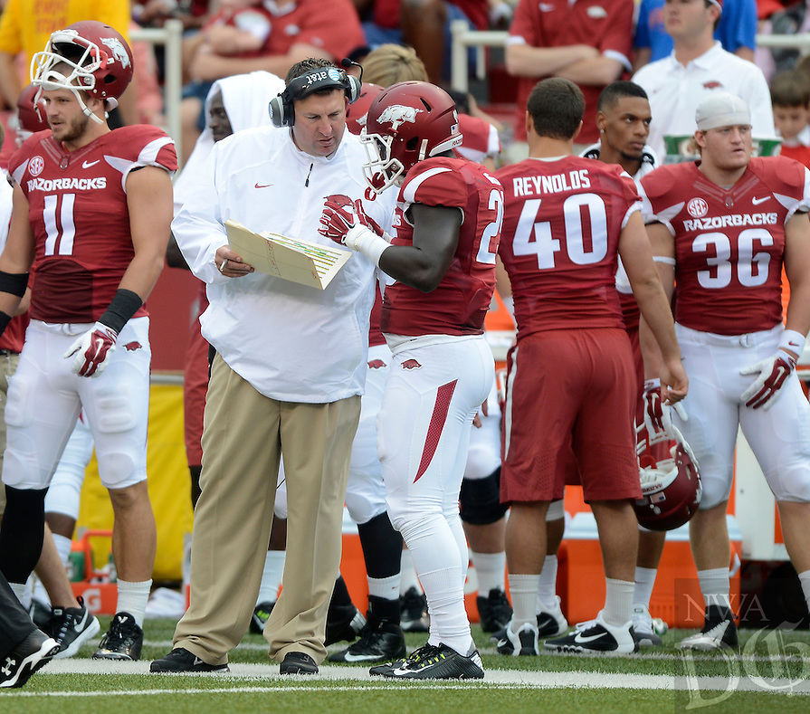 STAFF PHOTO ANTHONY REYES • @NWATONYR<br /> Bret Bielema, Arkansas head coach talks to Denzell Evans against Nicholls State in the first quarter Saturday, Sept. 6, 2014 at Razorback Stadium in Fayetteville.