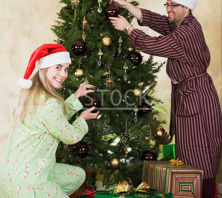 Couple wearing Santa hats and pajamas decorating Christmas tree