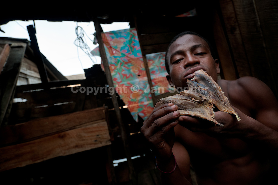 The Colombian fisherman Leonardo eats a dried fish in his wooden house in the poor neigbourhood outside of Tumaco, Colombia, 16 June 2010.