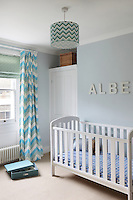 Zig-zag striped curtains hang at the window of this child's bedroom. A lampshade with a matching pattern in shades of green hangs from the ceiling light