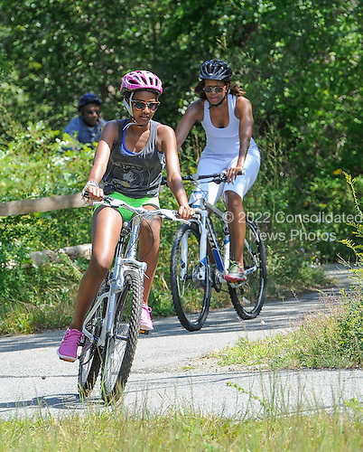 First lady Michelle Obama and daughter Sasha Obama bike riding during their vacation in West Tisbury on Martha's Vineyard, Massachusetts on August 16, 2013.  <br /> Credit: Rick Friedman / Pool via CNP