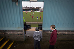 Two young spectators watching the first-half action as Port Talbot Town (in blue) play host to Caerau Ely in a Welsh Cup fourth round tie at the Genquip Stadium, formerly known as Victoria Road. Formed by exiled Scots in 1901 as Port Talbot Athletic, they competed in local and regional football before being promoted to the League of Wales  in 2000 and changing their name to the current version a year later. Town won this tie 3-0 against their opponents from the Welsh League, one level below the welsh Premier League where Port Talbot competed, watched by a crowd of 113.
