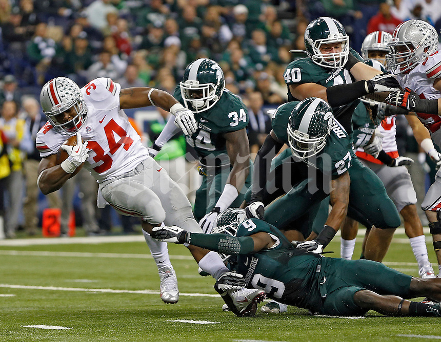 Ohio State Buckeyes running back Carlos Hyde (34) gets tripped up by Michigan State Spartans safety Isaiah Lewis (9) in the 3rd quarter during the Big 10 Championship game at Lucas Oil Stadium in Indianapolis, Ind on December 7, 2013.  (Dispatch photo by Kyle Robertson)