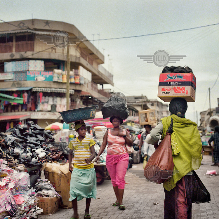 When walk through one of Accra's busiest markets carrying loads on their heads.