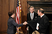 Elena Kagan, left, is congratulated by Chief Justice John Roberts, right, after becoming the Supreme Court's newest member Saturday, August 7, 2010, at the Supreme Court Building in Washington. The Bible was held by Jeffrey Minear, center, counselor to the chief justice. Kagan, 50, who replaces retired Justice John Paul Stevens, becomes the fourth woman to sit on the high court and is the first Supreme Court justice in nearly four decades with no previous experience as a judge. .Mandatory Credit: J. Scott Applewhite - Pool via CNP