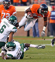 Oct 23, 2010; Charlottesville, VA, USA;  Virginia Cavaliers running back Perry Jones (33) leaps over Eastern Michigan Eagles cornerback Marty Cardwell (6) and Eastern Michigan Eagles running back Dwayne Priest (22) during the 1st half of the game at Scott Stadium.  Mandatory Credit: Andrew Shurtleff