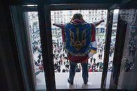 A protester wear a flag standing in a window of the  the Kiev city council building while  the Ukrainian  government's decide to stall on a deal that would bring closer ties with the European Union.