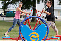 NWA Democrat-Gazette/DAVID GOTTSCHALK  Jamie Stephenson (left) and Stephanie Arthur use the new exercise equipment Wednesday, September 9, 2015 at Luther George Grove Street Park in Springdale. The two were playing with their children and began to use the equipment that was provided as a result of a joint use agreement grant through a partnership between the city of Springdale and the Springdale School District.